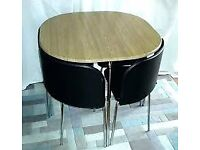Space saving table wood and black chairs