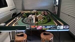 Slot car track set up on table, in good working condition.