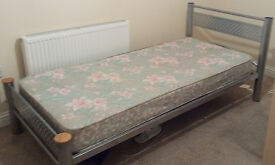 A metal single bed and its mattress for sale