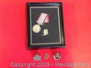 Confederation medal and three other pins or clips.