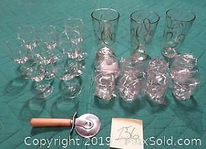 Eight Crown Royal shot glasses, 3 large glasses with gold trim, 8 small wine glasses, pizza cutter