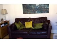 A 3 seater brown leather sofa bed
