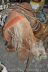 Saddle, saddle blanket, reigns and cowboy boots. -A
