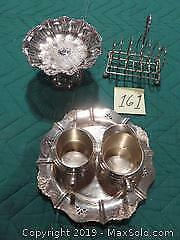 Silver plated: toast rack, fluted candy dish, cream and sugar on tray