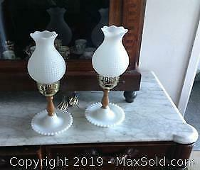 Two lamps fashioned from wood and milk glass.