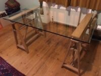 Large IKEA glass desk with wooden trestles.