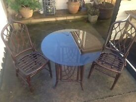 A glass/wooden table with two chairs. Suitable for Kitchen dinner or conservatory