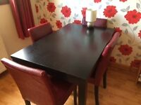 Black dining table with 4 red faux leather chairs