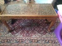 Coffee table carved asian style with carved legs and glass top