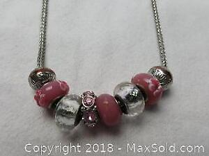Silver toned chain eighteen inches long with eight Pandora like charms shades of pink