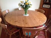 Solid Pine Circular table approx 1.4m in dia complete with 6 wooden chairs and covers
