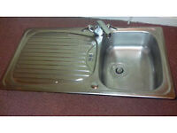 Stainless steel kitchen sink with mixer tap and flexi pipes.
