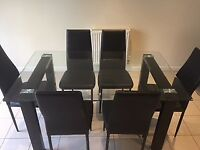 Glass kitchen/dining room table with 6 chairs. Less than 1 year old. Great condition