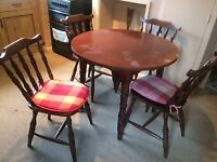 4 dark wood chairs good condition, including cushions, matching round table marked on top,to collect