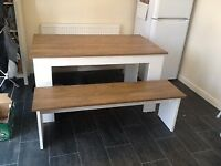 Dining table and 2 bench set. Melamine top in oak effect, with white melamine legs.