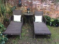 Pair of matching Rattan recliner sun loungers with side table.