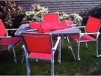 red xlarge patio dining table,4 solid armchairs xxlarge parasol & bbq, 2 bags of charcoal never used