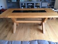 Heavy solid oak dining table, four chairs and sideboard with black glass inserts.