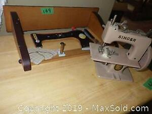 Metal Miniature Singer Sewing Machine and Shelf and Bolt of Cloth Upholstery A