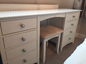 A white dressing table with drawers and a cushioned stool.