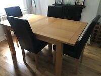 Oak dining table with brown leather chairs