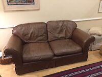 brown laura ashley two seater leather sofa. with loose cushions
