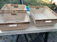 Set of four wicker baskets with handles.