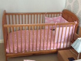 Light wood baby cot.