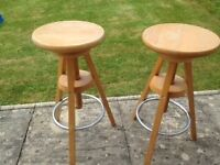 Two light-wood height adjustable stools for sale