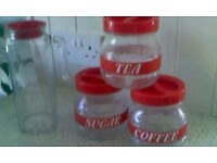 Glass kitchen caddies and Fridge jug set. Clear glass with red labels lids