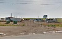 Commercial parking with site office, storage shed, and shelter.