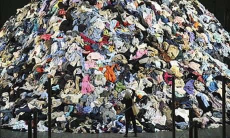 Lady in front of a clothing landfill