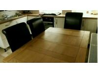 Solid Oak Extendeable Dinning Table and 6 brown leather chairs.