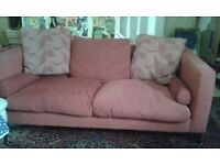 Red three seater sofa with two patterned cushions