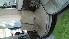 brown sofa and swivel chair