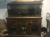 4 ft fish tank on antique cabinet, 1 dollar fish, 2 catfish, 2 heaters, 2 pumps & various orniments