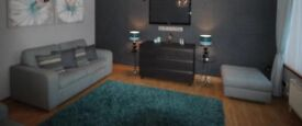 Two teal sofas and footstool