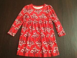 Long sleeved red dress with tree/leaf designs throughout dress