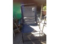 Four metal chairs and glass topped table patio set with parasol