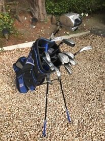 Golf bag and various clubs and a bag full of balls