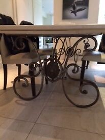 Large dining table, ornate metal base, stone (marble?) top, seats 8