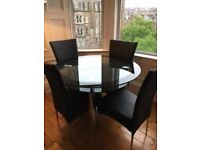 Glass dining table (round), including 4 black faux leather dining chairs