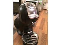 Nescafe Dolce Gusto Coffee Machine in Black with Stand & 2 Boxes of Cappuccino pods.