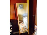 Tall wood-framed bedroom mirror on wheels