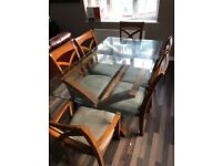 6 seater CLEAR GLASS DINING TABLE WITH WOODEN ARMS AND CLOTH FABRIC COVERING