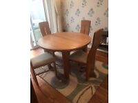 Oak extendable round dining table and four chairs.