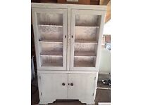 Pretty Shabby Chic storage with shelves lined in toile and cupboards below.