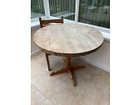 Round, solid pine dining table with pedestal leg