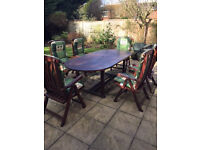 large oval shaped extending wooden garden table with six matching chairs and cushions