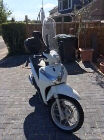 Honda 125 with stop/start function.Top box and tall screen. Tax only £19 per year.